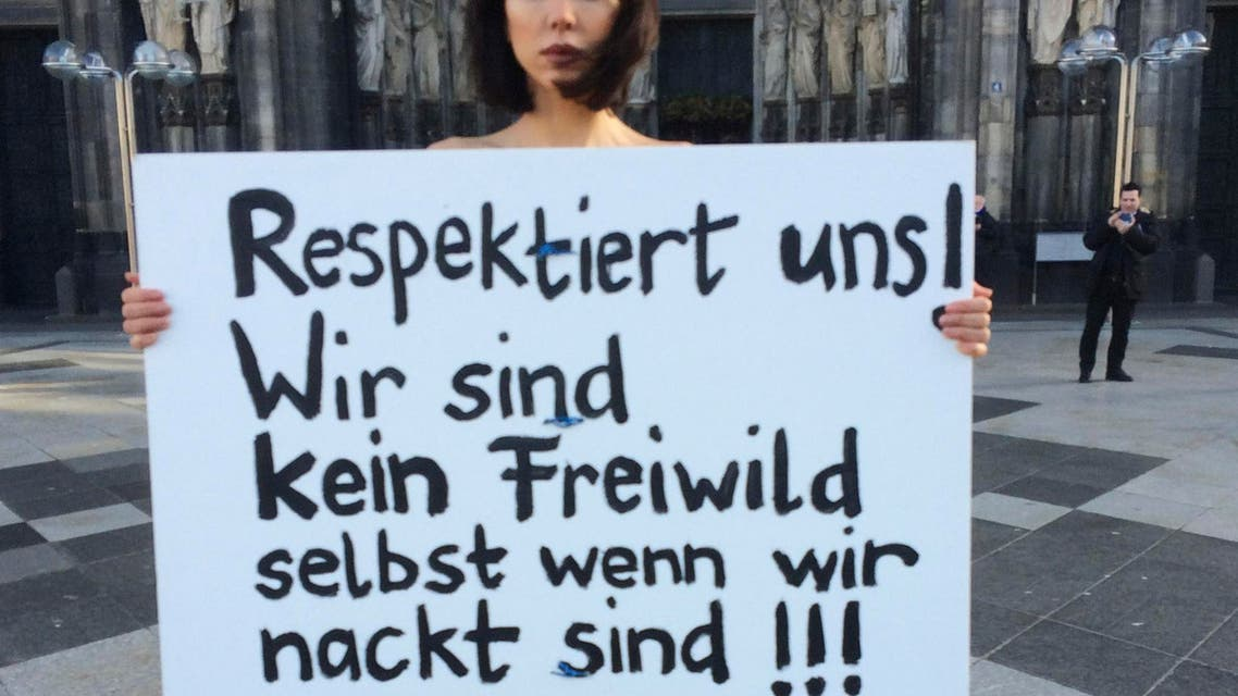 """CORRECTS YEAR - Swiss performance artist Milo Moire holds a sign """"Respect us! We are no fair game even when we are naked!!!"""" as she protests naked in front of the Cologne, western Germany, cathedral Friday, Jan. 8, 2016 following the sexual assaults and robberies during the New Year's Eve festivities in Germany. (AP Photo/Dorothee Thiesing)"""