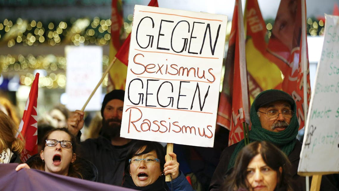 """Women shout slogans and hold up a placard that reads """"Against Sexism - Against Racism"""" as they march through the main railway station of Cologne, Germany, January 5, 2016. About 90 women have reported being robbed, threatened or sexually molested at the New Year's celebrations outside Cologne's cathedral by young, mostly drunk, men, police said on Tuesday. REUTERS/Wolfgang Rattay"""