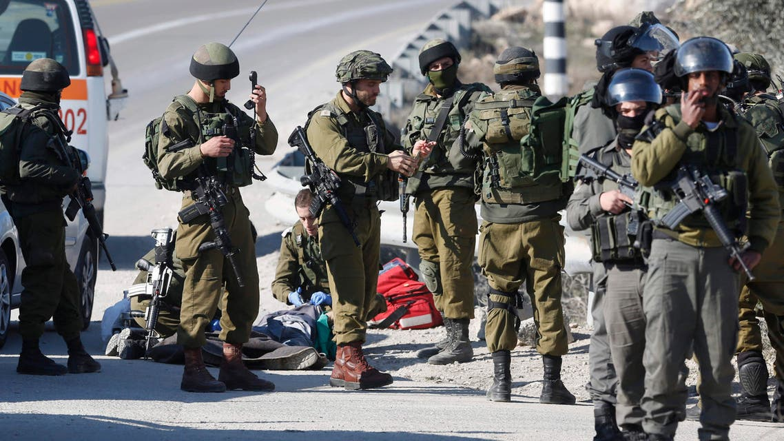 Israeli soldiers work around the body of a Palestinian assailant after he was shoot dead in the West Bank city of Hebron, Thursday, Dec. 24, 2015. ap