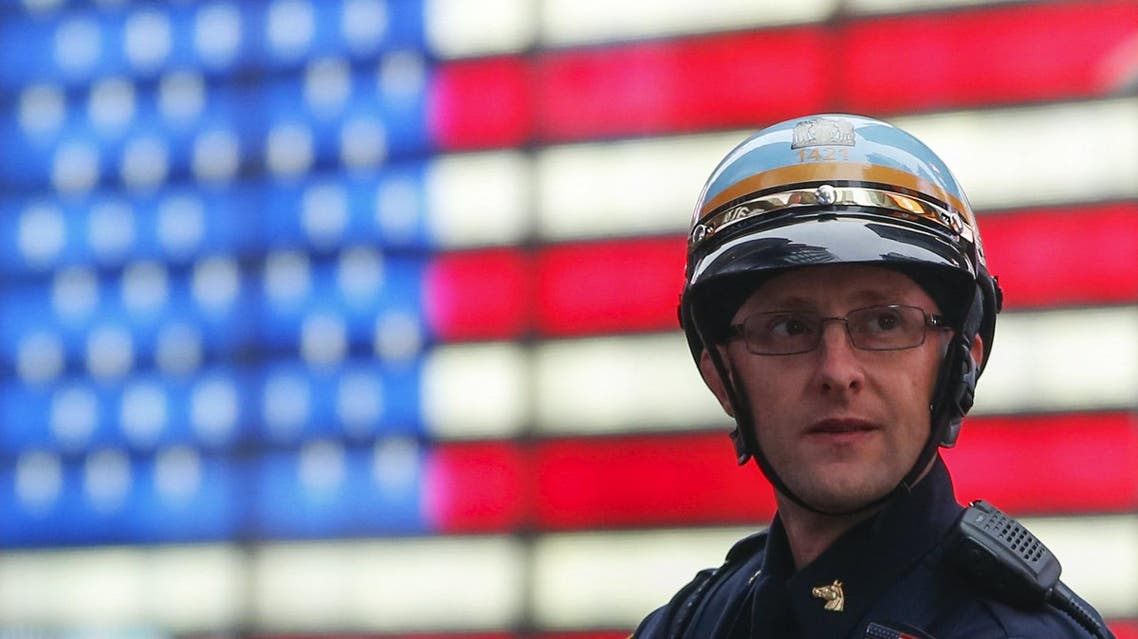 A New York Police Department (NYPD) officer with the mounted unit keeps guard from atop his horse (unseen) in front of a digital U.S. flag in Times Square, New York, December 14, 2015.
