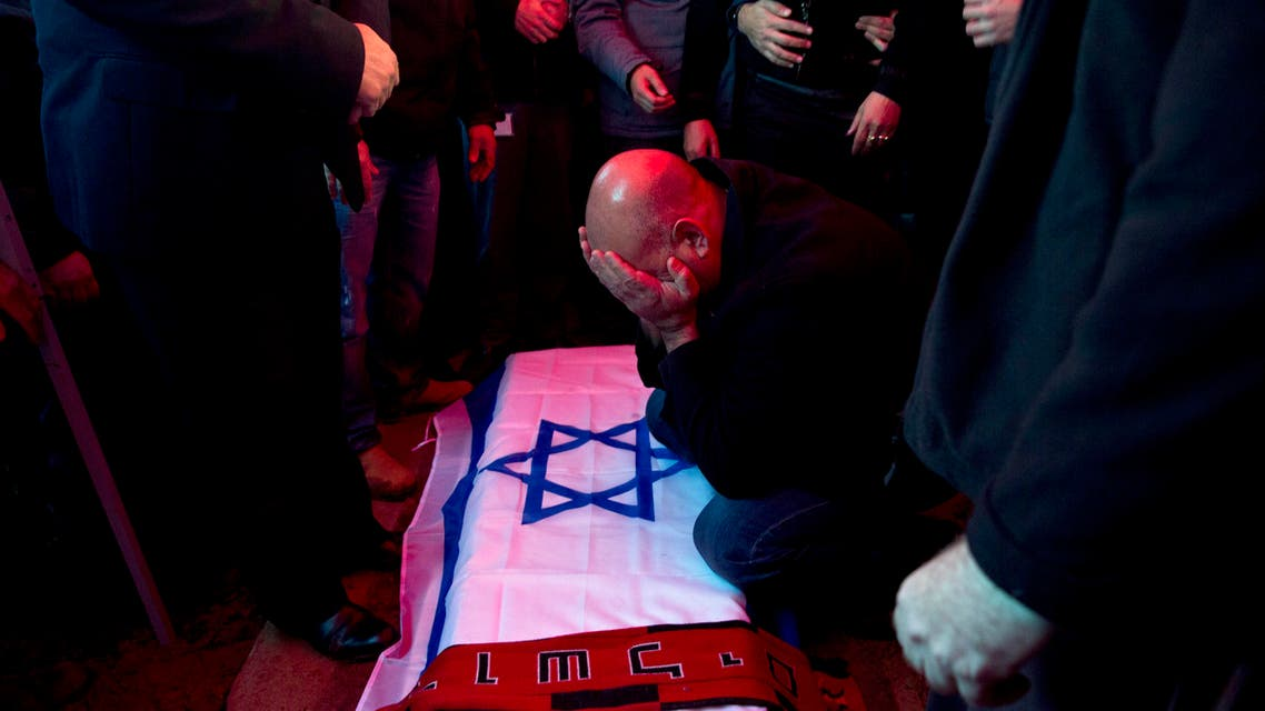 """David Bakal, father of Alon Bakal, who was killed when a gunman opened fire at a bar in Tel Aviv on Friday, mourns over his body during his funeral in Carmiel, northern Israel, Sunday, Jan. 3, 2016. Israeli police are on """"heightened alert"""" as they continue the manhunt for a gunman who killed two people and wounded several others Friday when he opened fire at a bar in Tel Aviv. (AP Photo/Ariel Schalit)"""