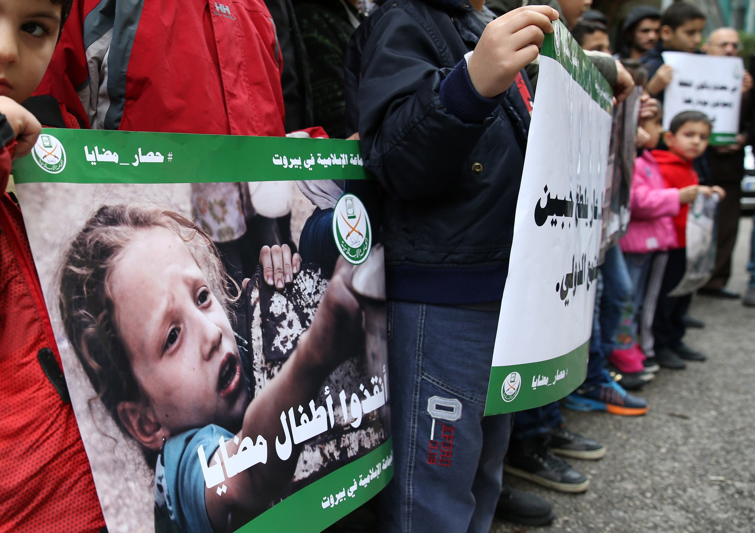 People carry posters during a sit-in calling for the lifting of the siege off Madaya, in front of the International Committee of the Red Cross in Beirut, Lebanon January 8, 2016. (AFP)