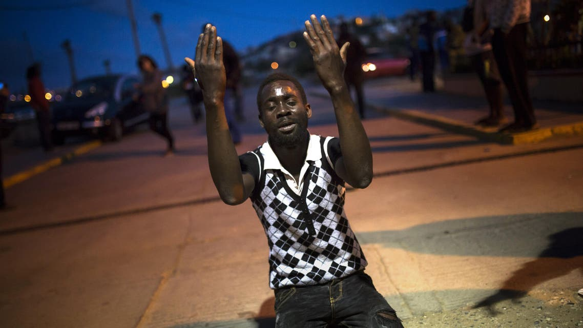A sub-Saharan migrant prays in front of a Temporary Centre for Immigrants (CETI) after scaling a metallic fence that divides Morocco and the Spanish enclave of Melilla, early in the morning on Wednesday, May 28, 2014. AP
