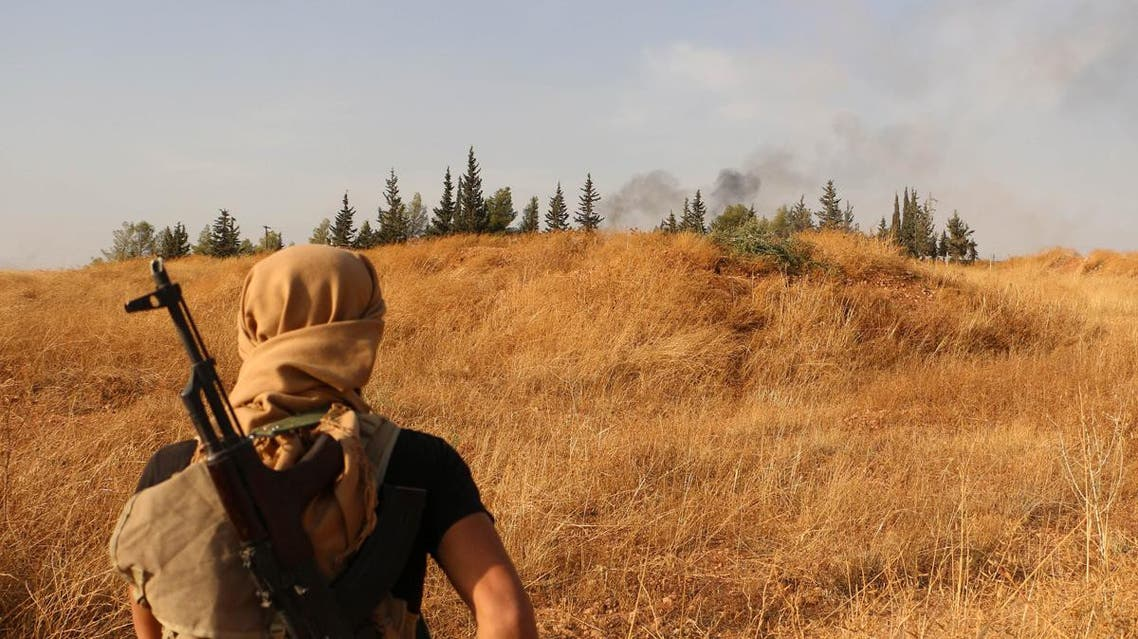 A rebel fighter looks at smoke billowing in the background during clashes with pro-government forces south of the northern Syrian city of Aleppo on October 19, 2015. (AFP)