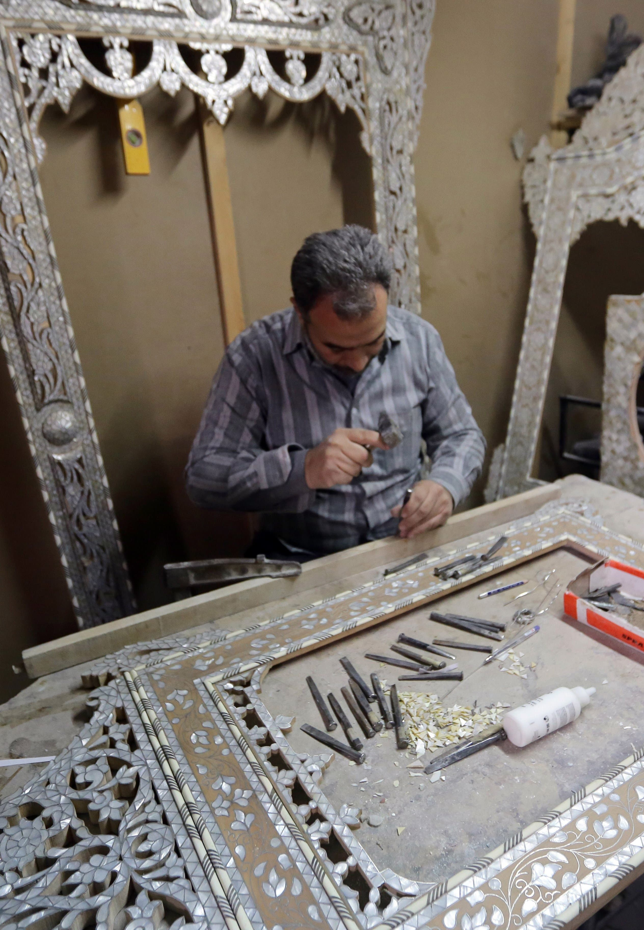 A Syrian artisan etches away at wooden panels inlaid with mother-of-pearl, at a workshop in the capital, Damascus, on December 1, 2015. AFP