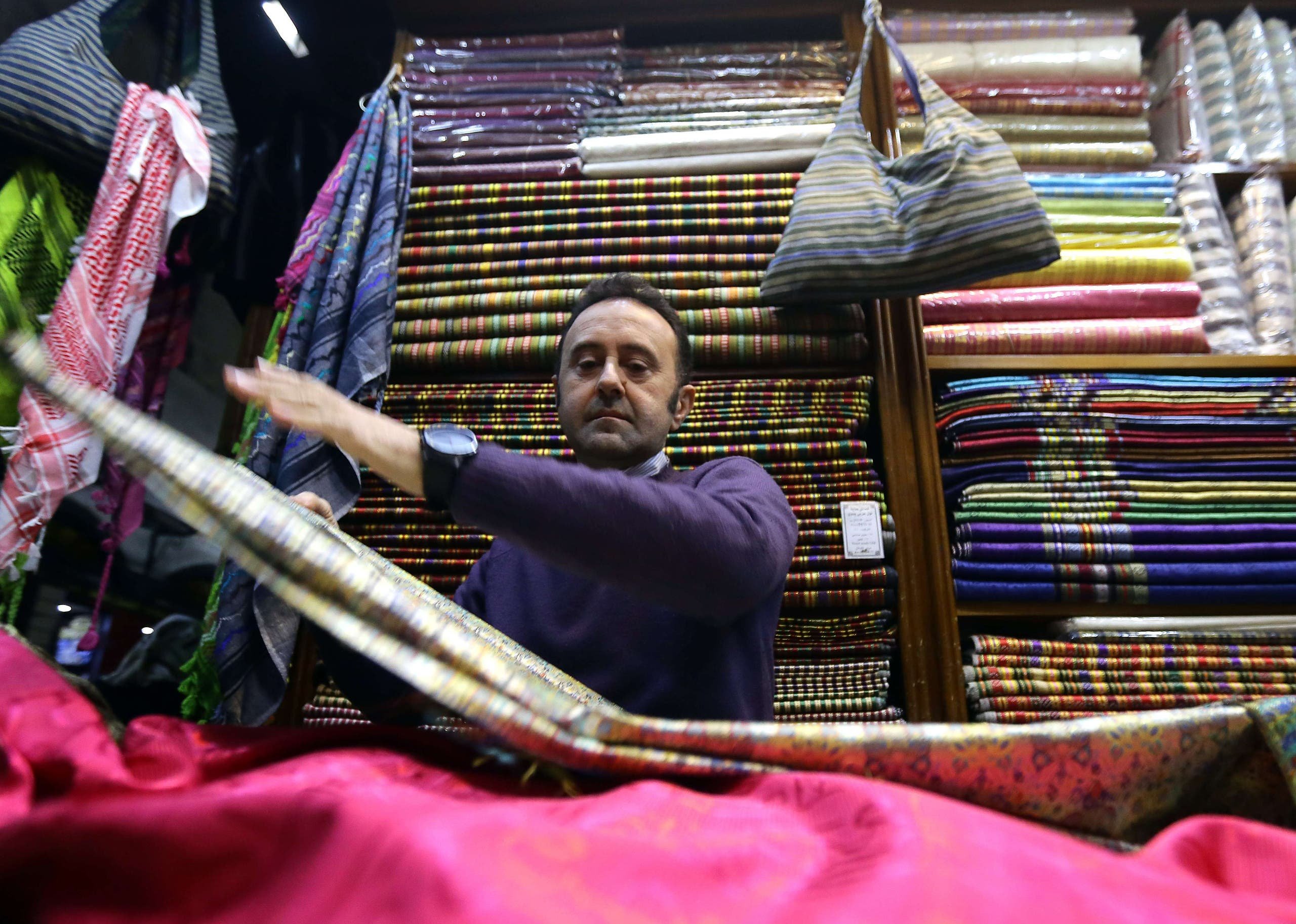 Bahaa al-Takriti, who weaves the richly embroidered aghbani cloths often used as table covers, shows off his products at his shop in the capital, Damascus, on December 1, 2015. AFP