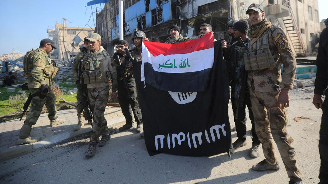 Members of the Iraqi security forces hold an Iraqi flag with an Islamic State flag which they had pulled down at a government complex in the city of Ramadi, December 28, 2015. REUTERS