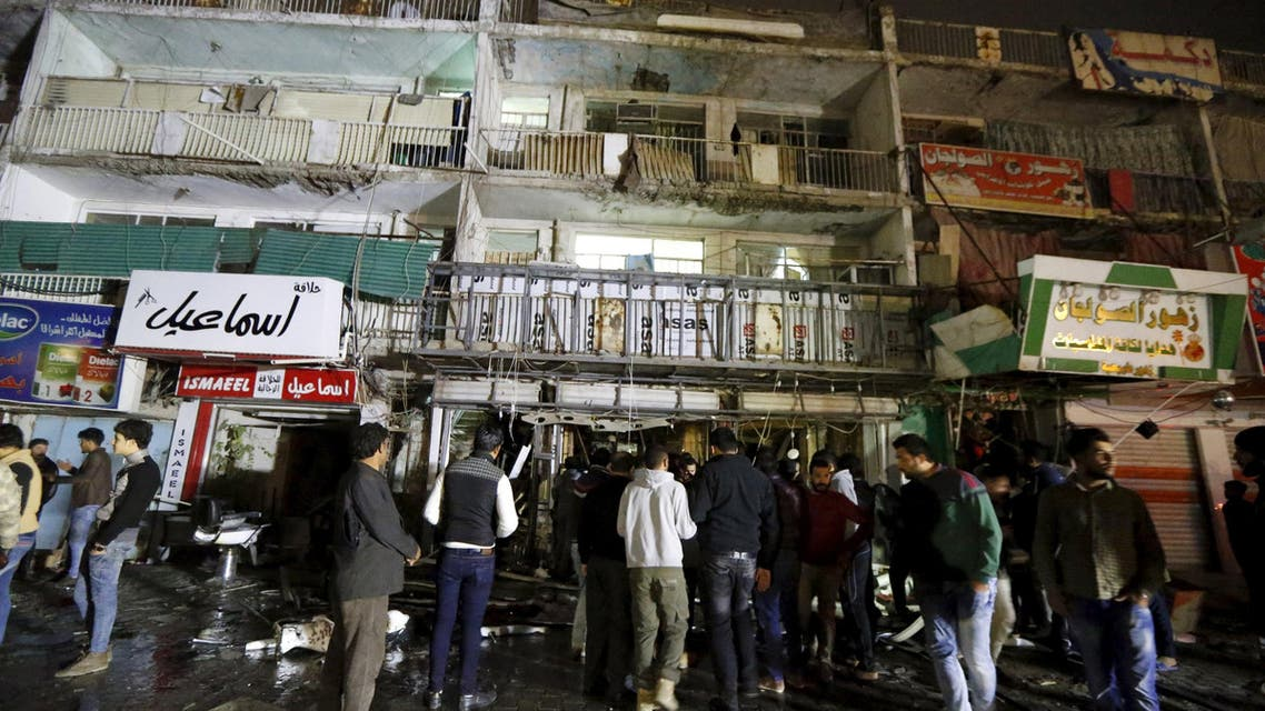 People gather at the site of a car bomb in New Baghdad, January 11, 2016. REUTERS