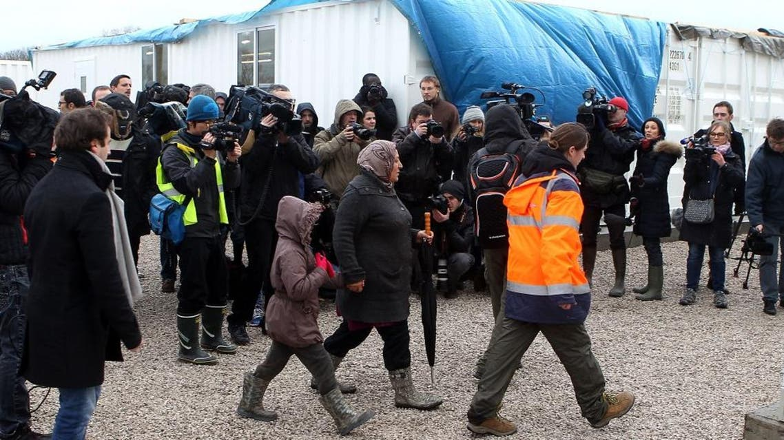 The first family of migrants arrive at their converted container, at the entrance of the Calais refugee camp, northern France, Monday, Jan. 11, 2016. Approximately 130 containers will be converted to shelters to accommodate as many as 1,500 migrants who are expected to move in on Jan. 11, 2016. (AP Photo/Michel Spingler)
