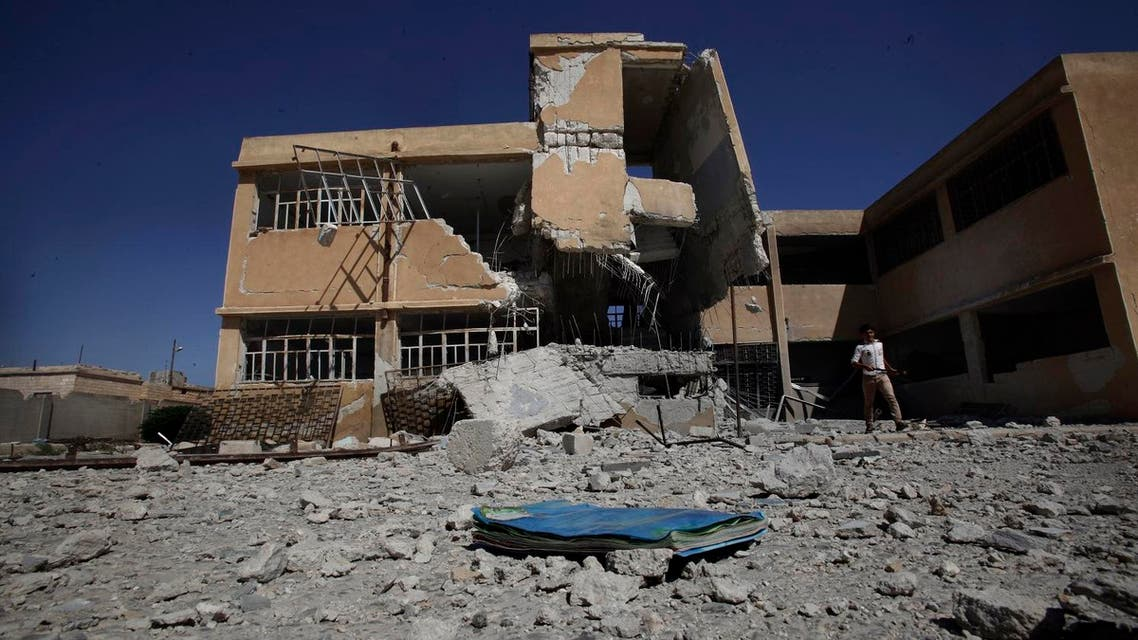 A book is left on the ground at the yard of a school destroyed in government airstrike in Tel Rifaat, on the outskirts of Aleppo, Syria, Sunday, Sept. 16, 2012. AP