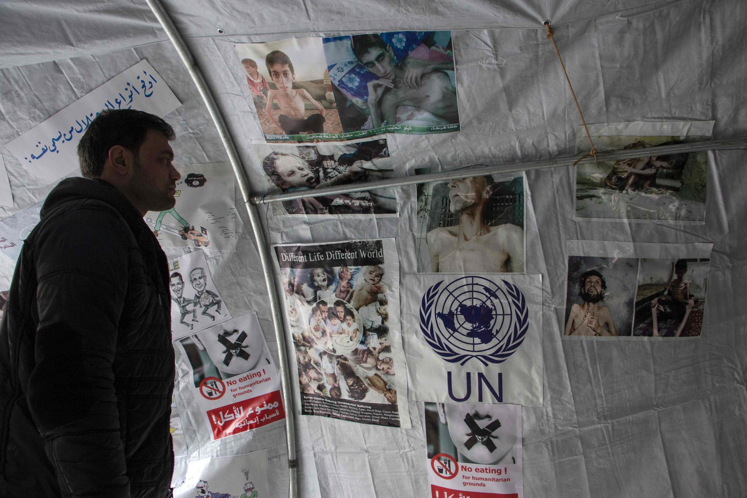 A Syrian man looks at pictures displayed under a tent during a demonstration on January 10, 2016 in the northern city of Aleppo in solidarity with the besieged town of Madaya. (AFP)