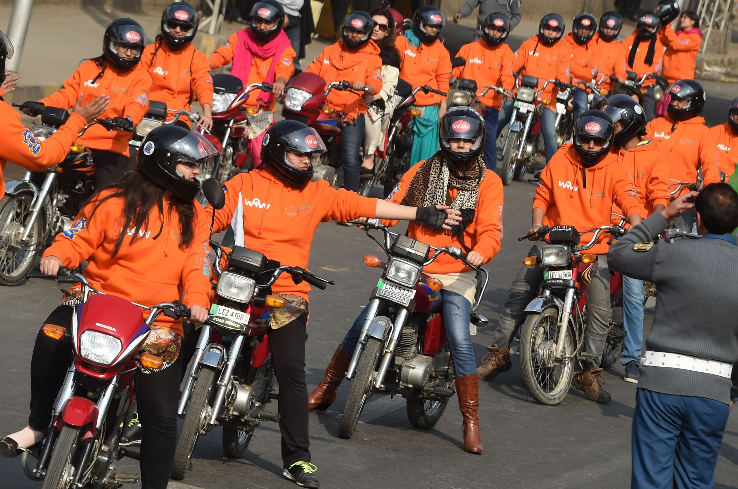 Women participants of Women on Wheels (WOW) wait on their motor-bikes prior to the start of a rally launching the Women on Wheels campaign in Lahore on January 10, 2016. (AFP)