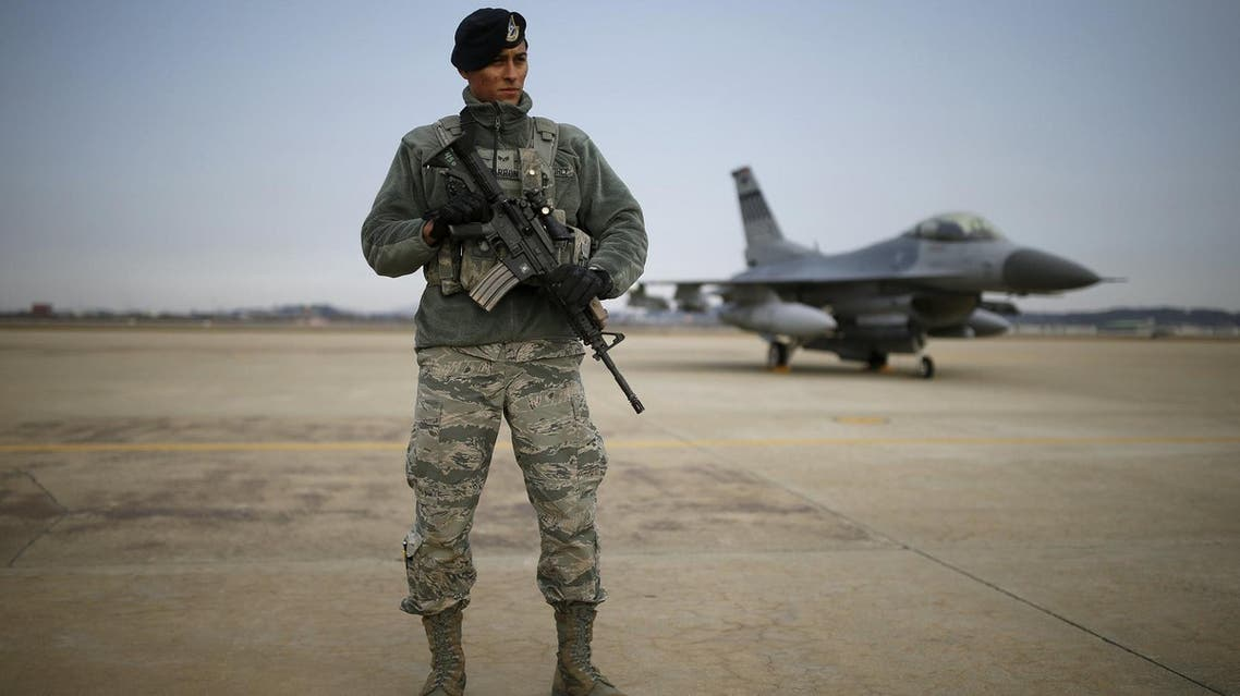 A U.S. soldier stands guard in front of their Air F-16 fighter jet at Osan Air Base in Pyeongtaek. (Reuters)