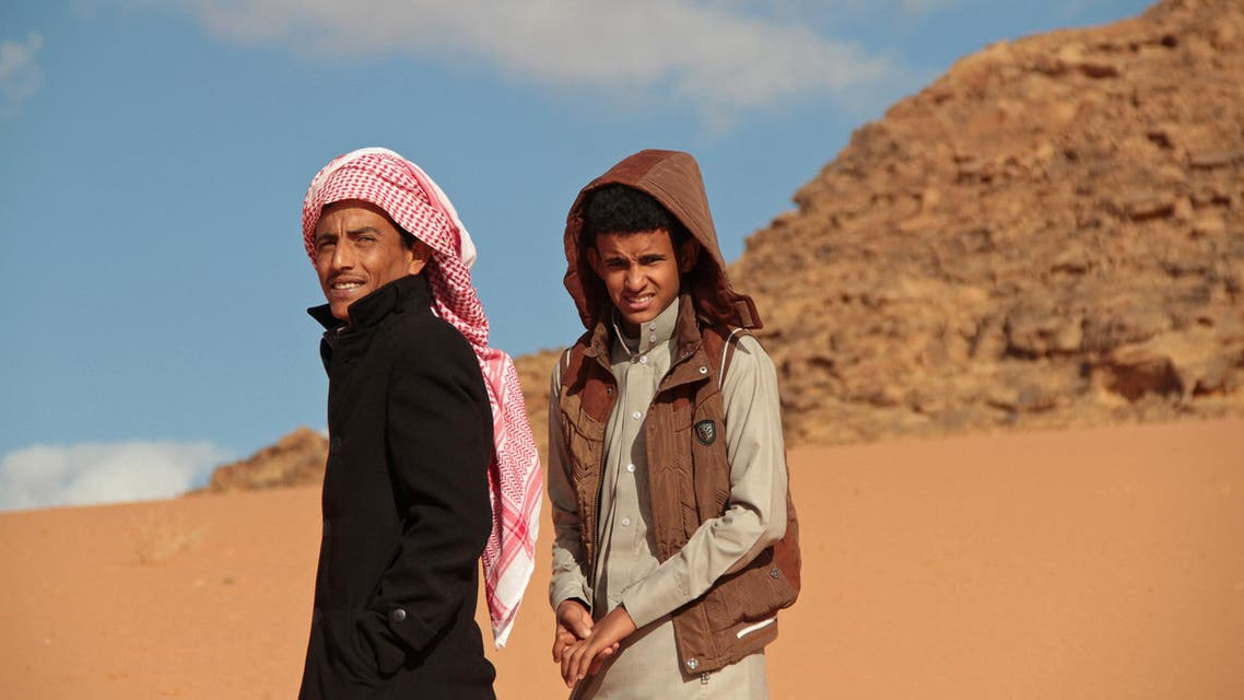"""In this Saturday, Jan. 9, 2016 Jacir Eid Al-Hwietat, right, and his cousin, Hussein Salameh al-Sweilhiyeen, pose for a photo in Wadi Rum, a scenic desert area of southern Jordan. Jacir and al-Sweilhiyeen, both from a Bedouin clan, acted in the film """"Theeb"""" (Wolf), a coming-of-age drama set in 1916, that has emerged as the first Oscar contender of Jordan's nascent film industry. The final five will be announced Thursday. (AP Photo/ Raad Adayleh)"""