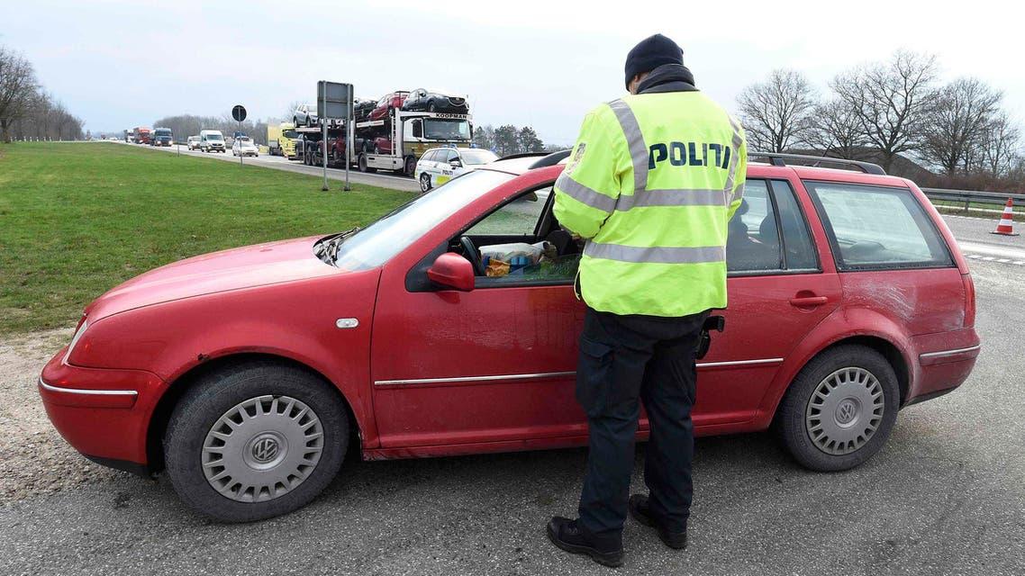 شرطي دنماركي يدقق في أوراق سيارة تعبر من المانيا الدنمارك دنمارك