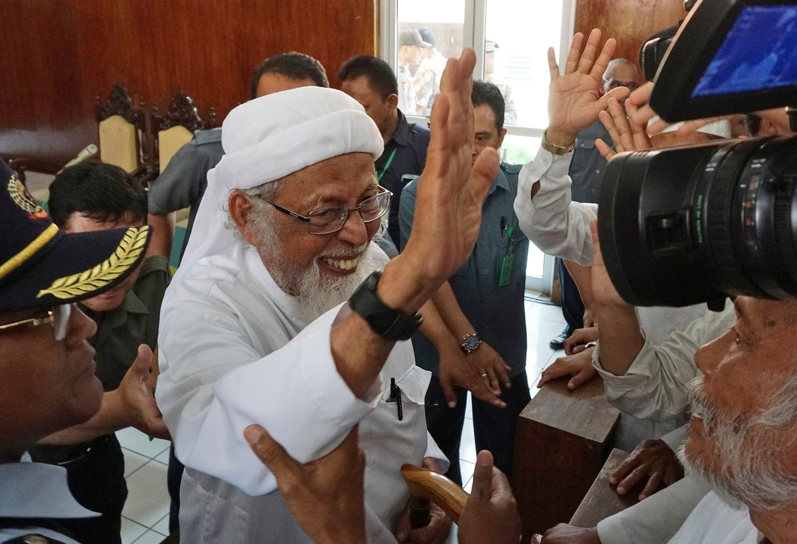 Radical Islamic cleric Abu Bakar Bashir, center, waves at his supporters after his appeal hearing at the local district court in Cilacap, Central Java, Indonesia, on January 12, 2016. (AP )