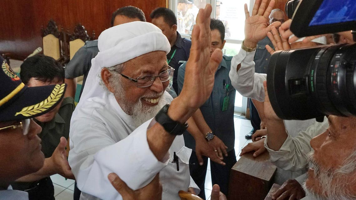 Radical Islamic cleric Abu Bakar Bashir, center, waves at his supporters after his appeal hearing at the local district court in Cilacap, Central Java, Indonesia, Tuesday, Jan. 12, 2016. The Indonesian court heard the start of an appeal by the 77-year-old cleric who was sentenced to 15 years in jail in 2011 for setting up a terror training camp in the province of Aceh. (AP Photo/Agus Fitrah)