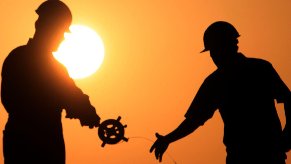 Oil men work on a new oil rig at sunset Thursday, April 1, 2010, in the Persian Gulf desert oil field of Sakhir, Bahrain.  (AP)