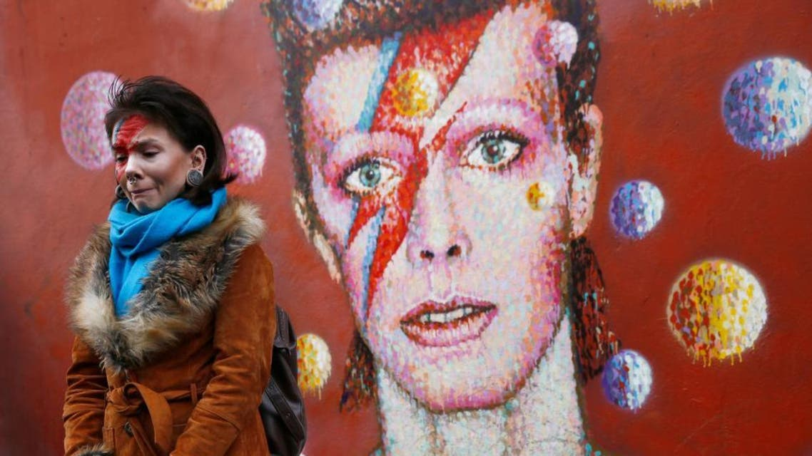 A woman wearing Ziggy Stardust-style make-up reacts as she visits a mural of David Bowie in Brixton, south London, January 11, 2016. (Reuters)