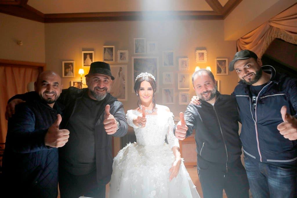 ديانا مرتدية فستان الزفاف وإلى جانبها فريق التصوير