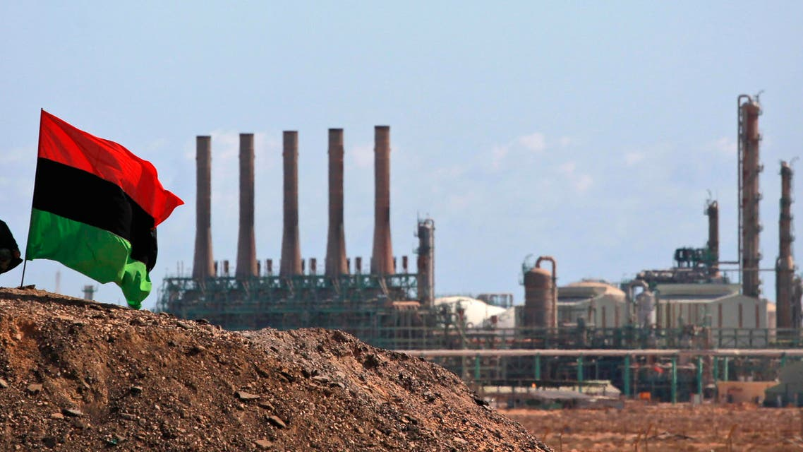 A Libyan rebel sits next to the country's flag as he guards outside the refinery in Ras Lanuf, eastern Libya. (Reuters)