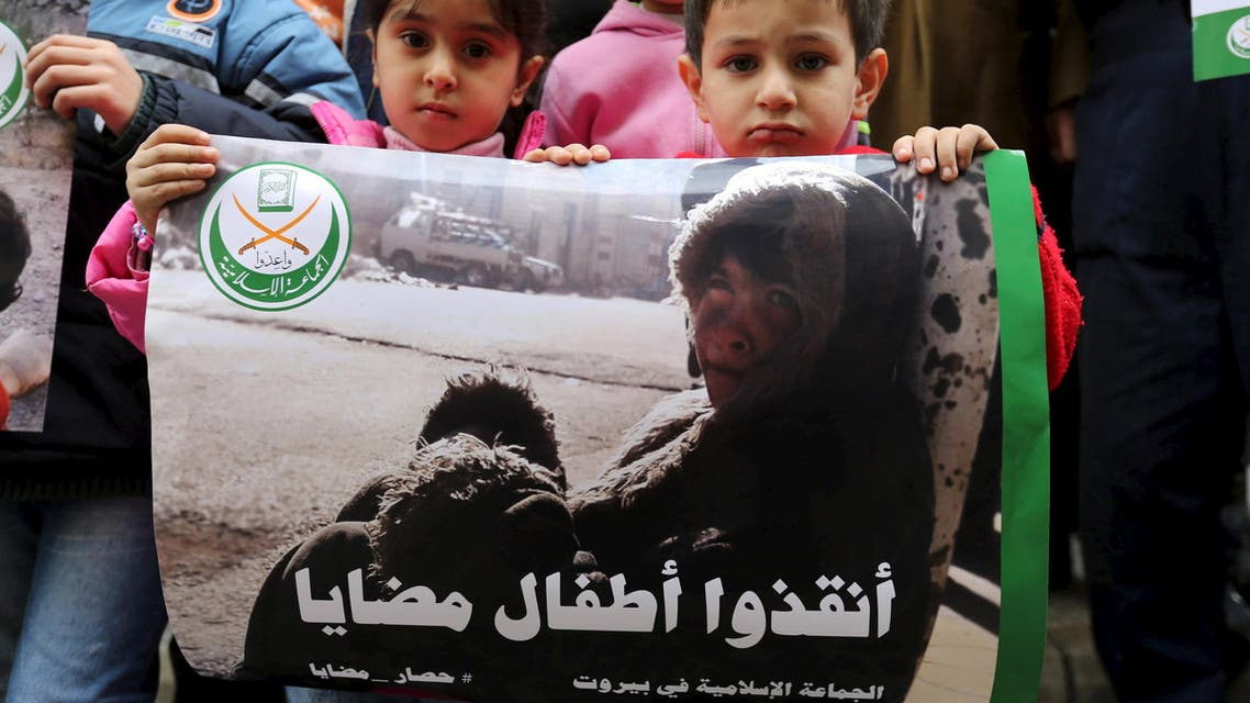 Children hold a poster during a sit-in organised by the Sunni Al Jama'a al-Islamiya group, calling for the lifting of the siege off Madaya, in front of the International Committee of the Red Cross (ICRC) in Beirut, Lebanon January 8, 2016.