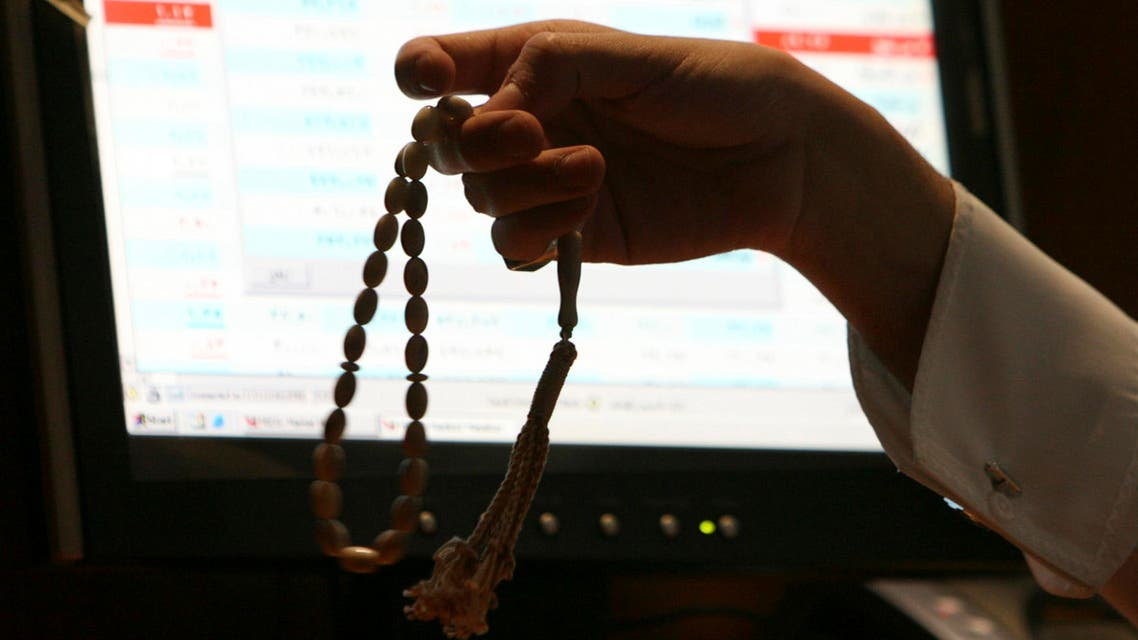 A Saudi trader holds prayer beads as he works at the Saudi Investment Bank in Riyadh (File photo Reuters)
