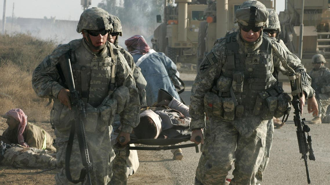U.S. soldiers of 3rd Brigade Combat team, 3rd Infantry Division carry an injured Iraqi volunteer civilian, following the second roadside bomb explosion of the day during the Sukhumi clearing operation in the area of Al-leg, some 60 kilometers (40 miles) south of Baghdad, Iraq, Friday, March 7, 2008.