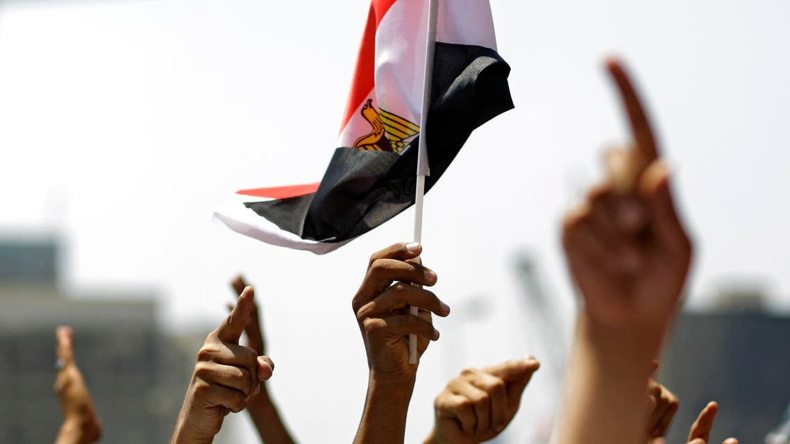 """People raise hands and wave Egyptian flag during a rally after Friday prayers in Tahrir Square in Cairo, Friday, July 1, 2011. Hundreds of people were rallying in the square, that was the epicenter of the uprising that toppled Hosni Mubarak, demanding speedy trials for former regime figures and policemen accused of killing protesters during the 18-day revolt earlier this year. The rally is dubbed """"Friday of Retribution"""" to reflect what protesters perceive as a slow pace of trials of former officials, nearly five months after Mubarak's Feb. 11 ouster.(AP Photo/Sergey Ponomarev)"""