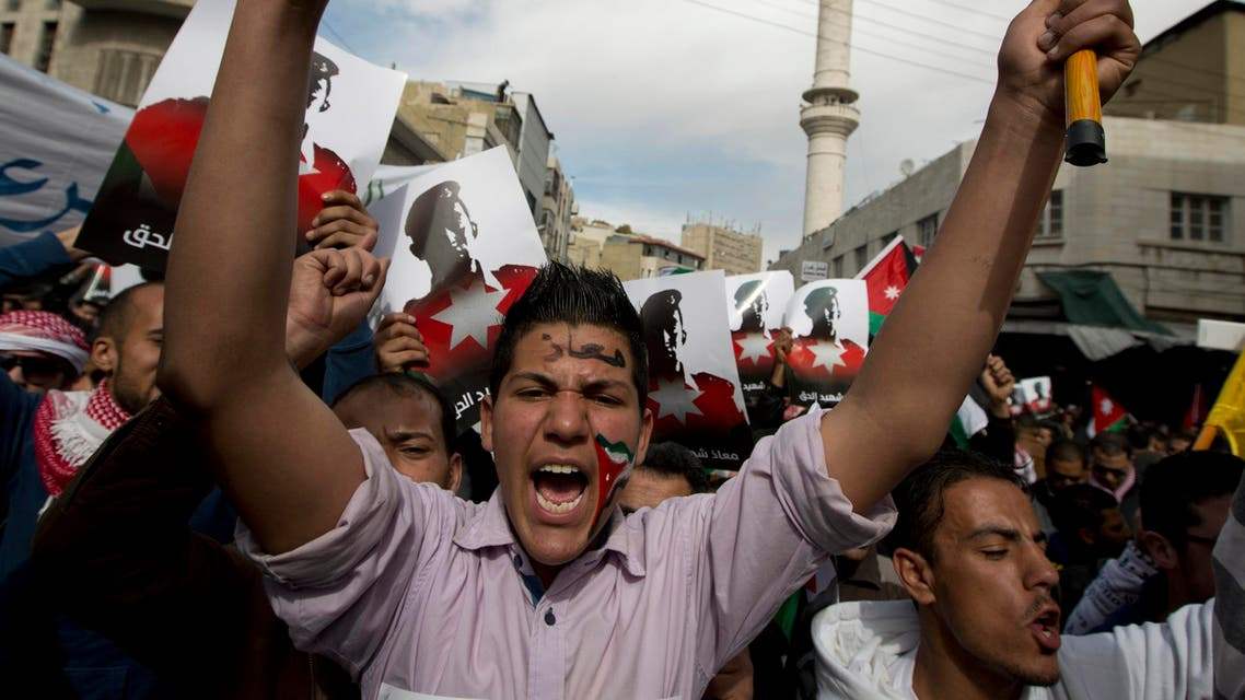 """Demonstrators, one painting his national flag and Arabic that reads """"Muath,"""" chant anti-Islamic State group slogans and carry posters with pictures of slain Jordanian pilot, Lt. Muath al-Kaseasbeh, during an anti-IS group rally in Amman, Jordan, Friday, Feb. 6, 2015."""