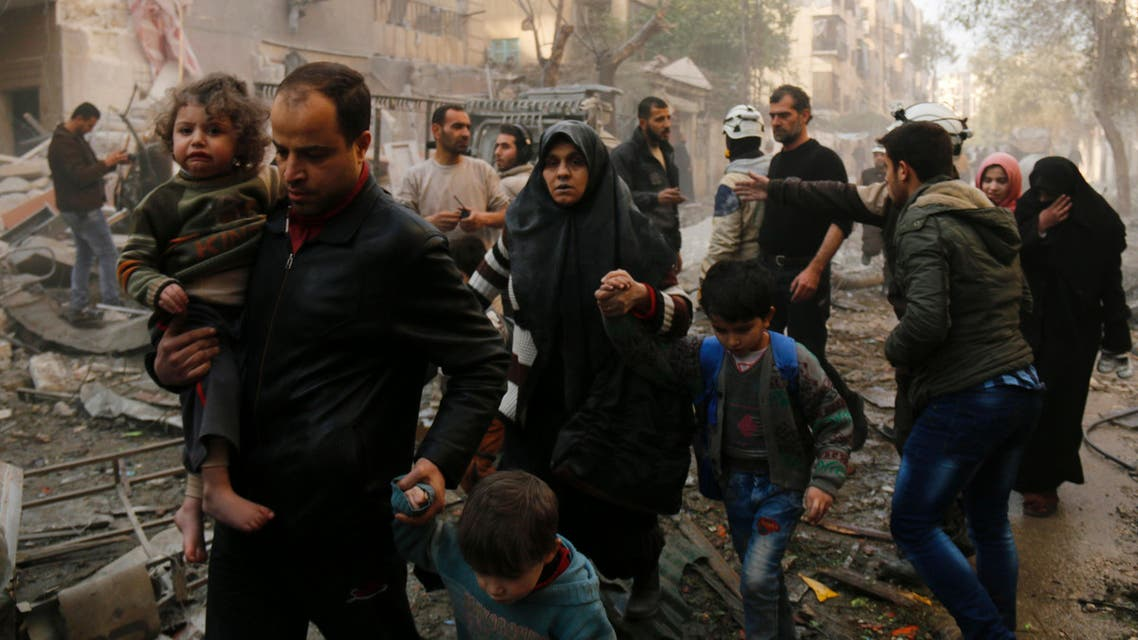 Syrians make their way through debris as they leave for a safer place following air strikes in the rebel-controlled side of the northern city of Aleppo on January 13, 2016. (AFP)