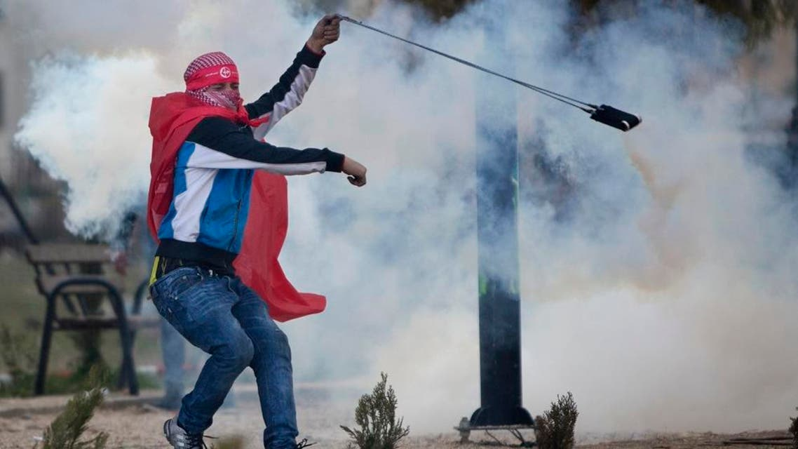 Palestinian demonstrators uses a slingshot to throw back a tear gas canister at Israeli troops following a rally marking the 48th anniversary of the founding of the Popular Front for the Liberation of Palestine (PFLP), in the West Bank, near Ramallah, Saturday, Dec. 12, 2015. (AP Photo/Majdi Mohammed)