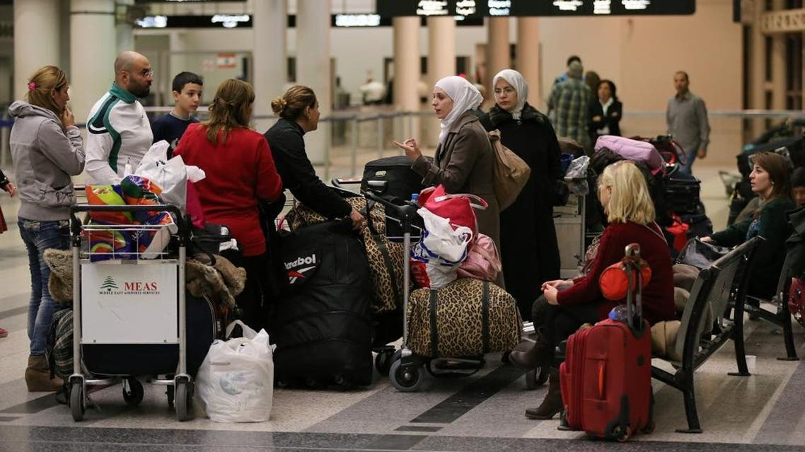 """In this Friday, Nov. 20, 2015 file photo, travellers stand next to their luggage at the departure terminal of Rafik Hariri international airport, in Beirut, Lebanon. A Lebanese official said on Friday, Jan. 15, 2016 reports that Beirut International Airport doesn't meet international safety standards are """"exaggerated"""" but acknowledged that the facility needs improvement. (AP Photo/Hussein Malla, File)"""