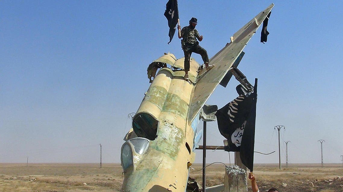 In this undated file photo posted on Wed. Aug. 27, 2014 by the Raqqa Media Center of ISIS, which has been verified and is consistent with other AP reporting, fighters of the Islamic State wave the group's flag from a damaged display of a government fighter jet, in Raqqa, Syria. AP