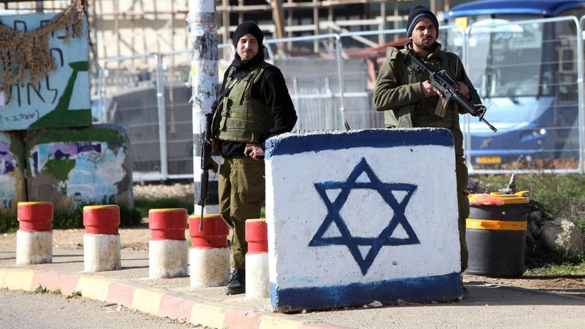 Israeli soldiers stand guard at the Gush Etzion junction in the West Bank following an attack. Tuesday, Jan. 5, 2016. A Palestinian attacker stabbed an Israeli soldier on Tuesday in the West Bank, lightly wounding him before troops at the scene shot and killed the assailant, the military said. (AP Photo/Mahmoud Illean)