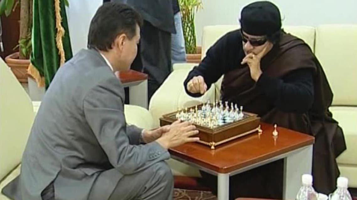 A video image of World Chess Federation president Kirsan Ilyumzhinov playing chess with then Libyan leader Muammar Qaddafi in Tripoli, in 2011 (AFP Photo/HO)