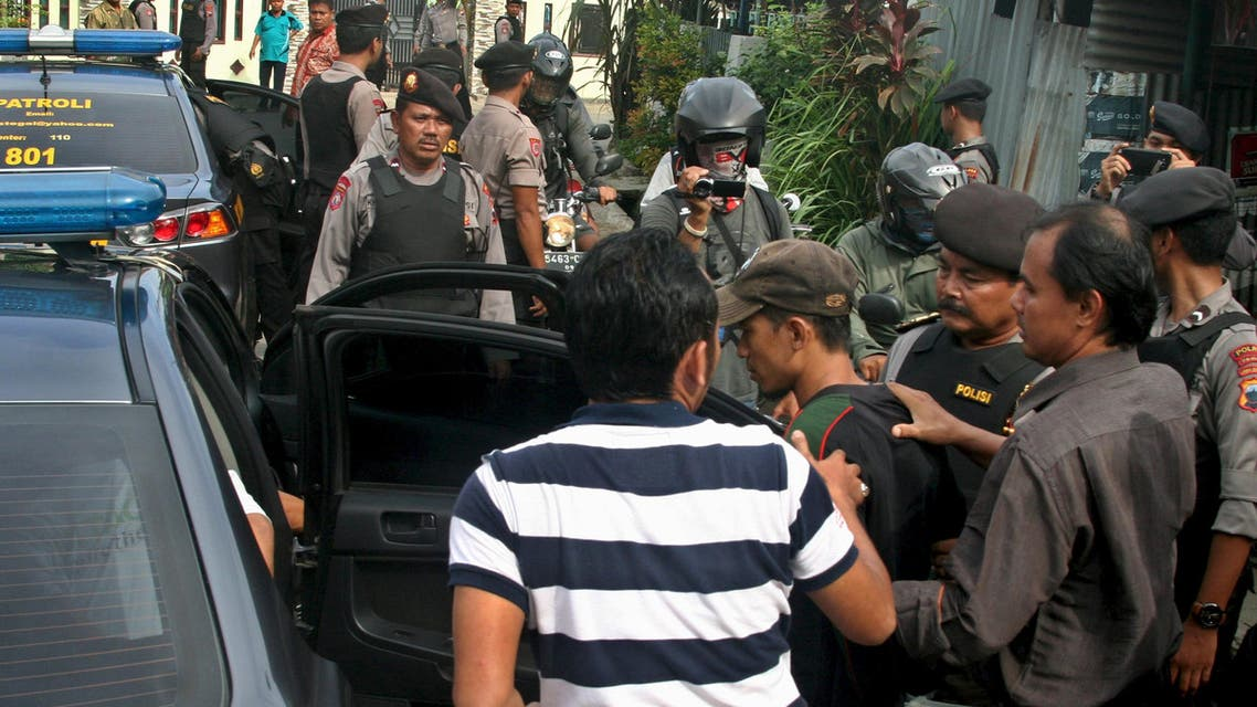 Police officers escorts a man (C, with a cap) who was arrested during a raid in the Langgen village in Tegal, Indonesia Central Java, January 15, 2016 in this photo taken by Antara Foto. Indonesia's police chief said on Saturday security forces have arrested 12 people linked to this week's attack by Islamic State militants in the centre of Jakarta. REUTERS/Oky Lukmansyah/Antara Foto ATTENTION EDITORS - THIS IMAGE HAS BEEN SUPPLIED BY A THIRD PARTY. IT IS DISTRIBUTED, EXACTLY AS RECEIVED BY REUTERS, AS A SERVICE TO CLIENTS. FOR EDITORIAL USE ONLY. NOT FOR SALE FOR MARKETING OR ADVERTISING CAMPAIGNS. MANDATORY CREDIT. INDONESIA OUT. NO COMMERCIAL OR EDITORIAL SALES IN INDONESIA.