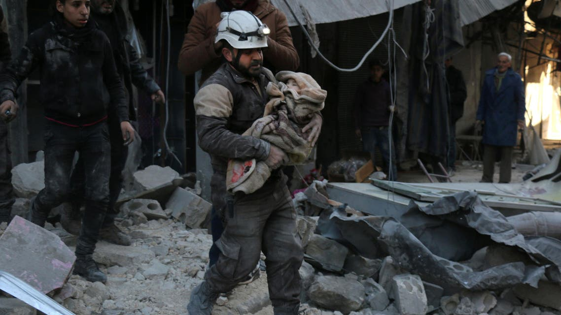 A Syrian Civil Defence worker carries a child wrapped in a blanket over the rubble following a reported air strike by Syrian government forces on the Sukkari neighborhood of Syria's northern city of Aleppo, on January 16, 2016. (AFP)