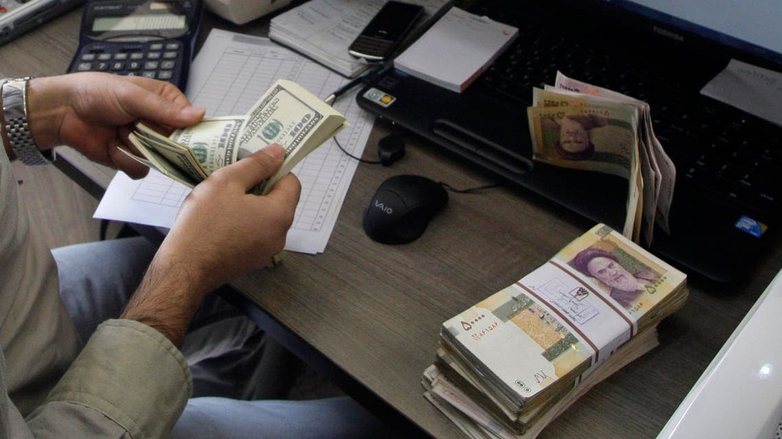 A currency exchange bureau worker counts US dollars, as Iranian bank notes are seen at right AP