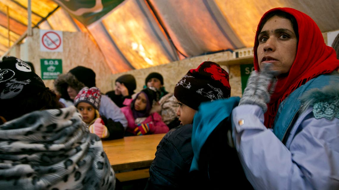 Migrants wait inside a tent to keep warm before departing from the registration camp after crossing from the Macedonian border into Serbia, in Presevo, Serbia, Sunday, Jan. 17, 2016. Despite cold temperatures and snow storms hundreds of migrants continue to arrive daily into Serbia in order to register and continue their journey further north towards Western Europe. (AP Photo/Visar Kryeziu)