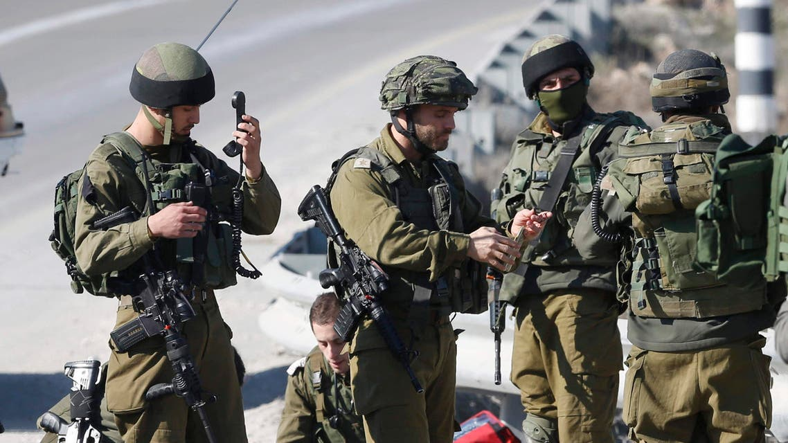 Israeli soldiers work around the body of a Palestinian assailant after he was shoot dead in the West Bank city of Hebron, Thursday, Dec. 24, 2015. (AP)
