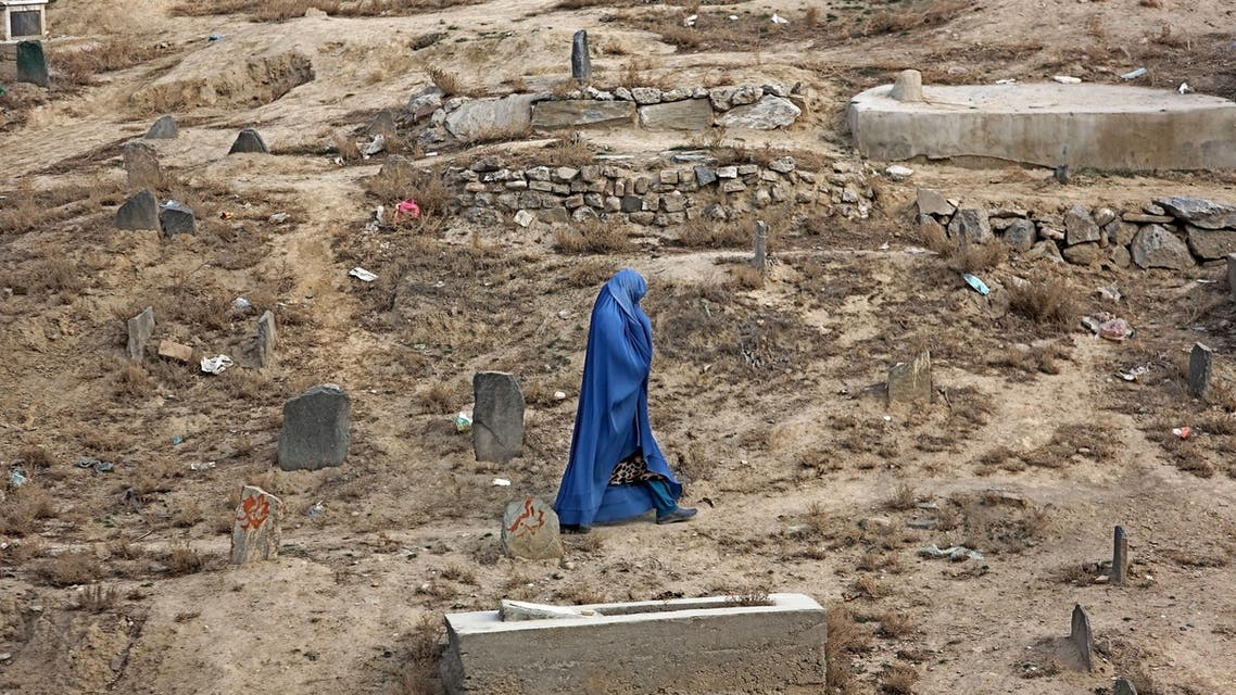 An Afghan woman walks at a cemetery in Kabul, Afghanistan, Tuesday, Dec. 8, 2015. (AP
