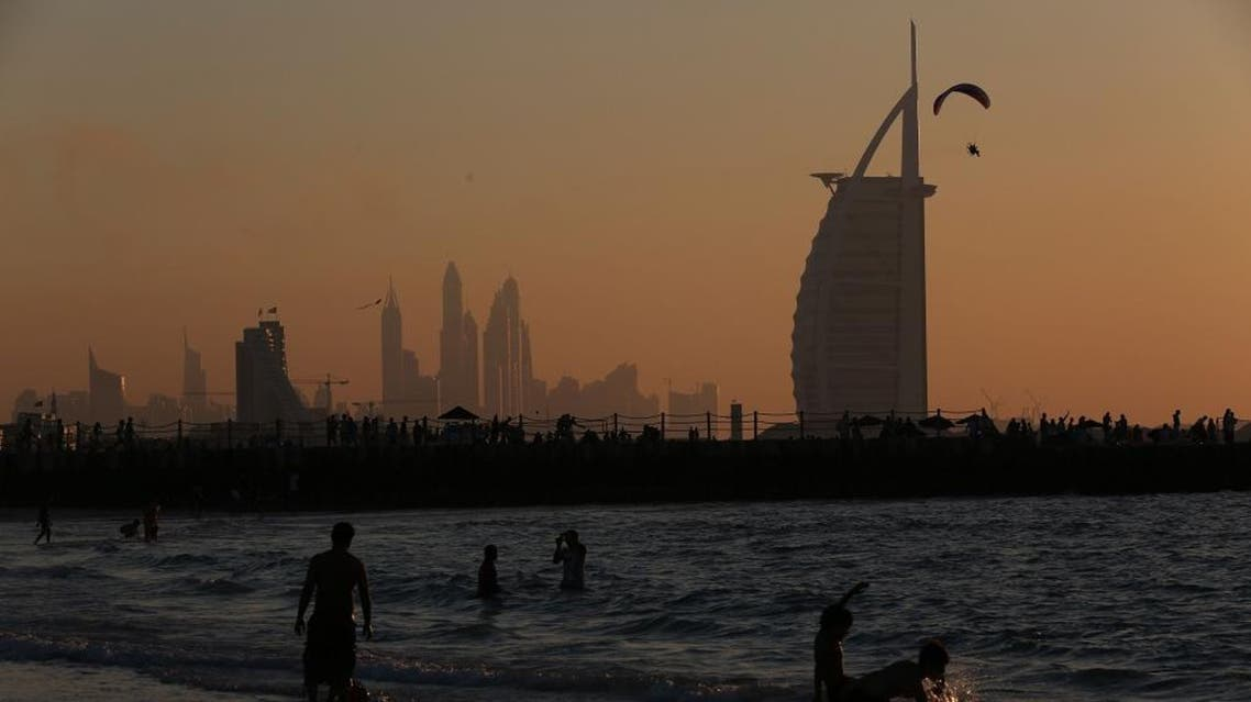Children play in the surf at Kite Beach with the Burj al Arab, the Dubai Marina and a man flying a powered parachute in the background in Dubai, United Arab Emirates, on Friday, Jan. 8, 2016. (AP Photo/Jon Gambrell)