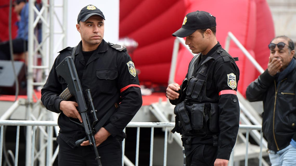 Tunisian policemen, wearing red armbands in protest over low wages and difficult working conditions, stand guard on Habib Bourguiba avenue in Tunis on January 18, 2016. / AFP