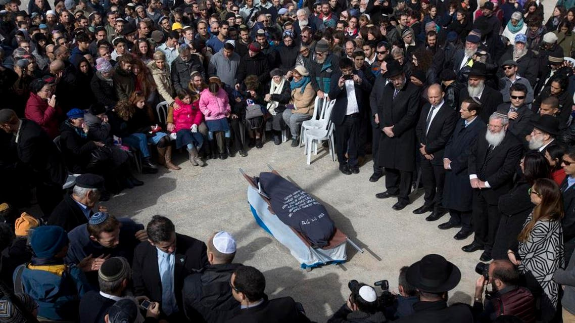 Family and friends of Israeli Dafna Meir attend her funeral in a cemetery in Jerusalem Monday, Jan. 18, 2016. A Palestinian broke into a West Bank settlement home and fatally stabbed an Israeli woman before fleeing Sunday, touching off a massive night manhunt, the Israeli military said. (AP Photo/Sebastian Scheiner)