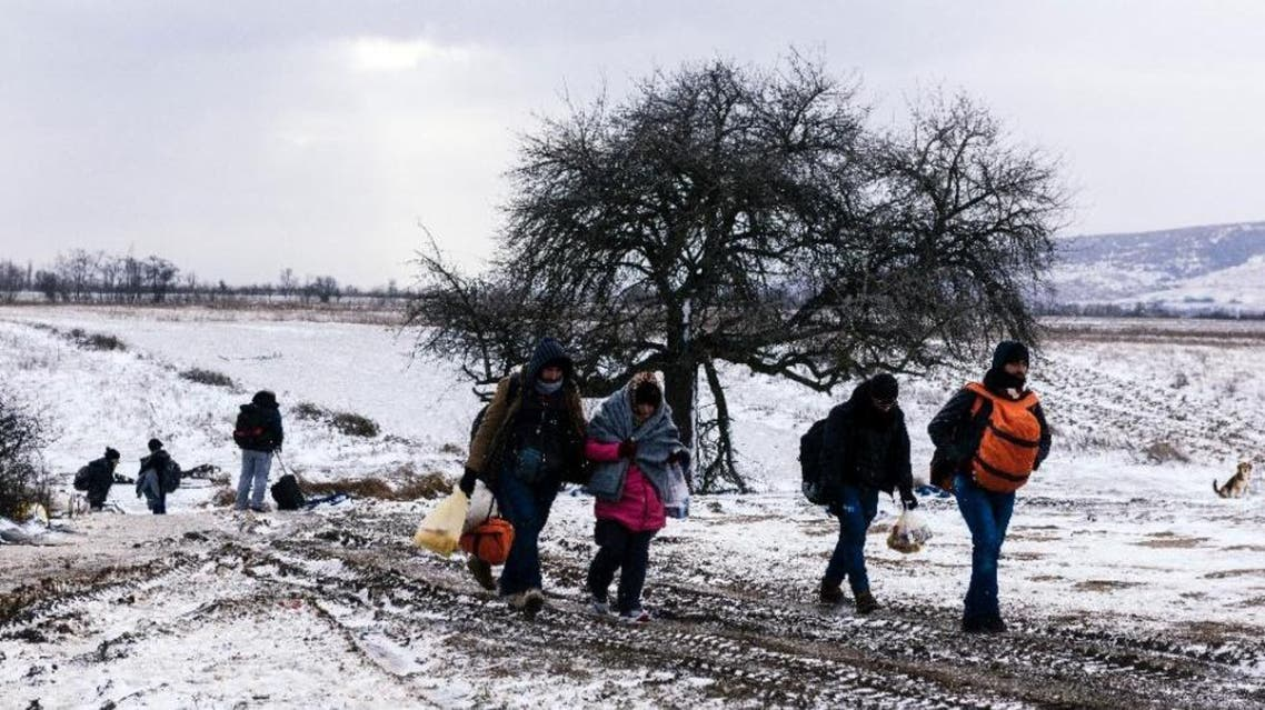Migrants walk through the snow after crossing the Macedonian border into Serbia near the village of Miratovac on January 18, 2016 (AFP)