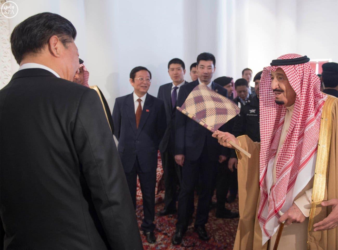 الملك سلمان يحمل مروحة كان يستخدمها السعوديون قديماً