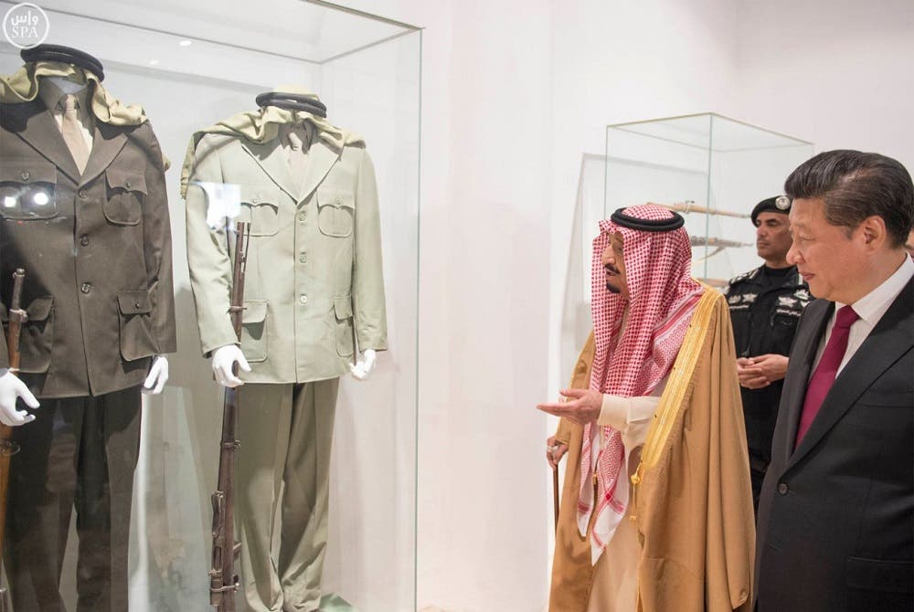 Saudi King Salman with Chinese President Xi Jinping displaying a collection of military uniforms