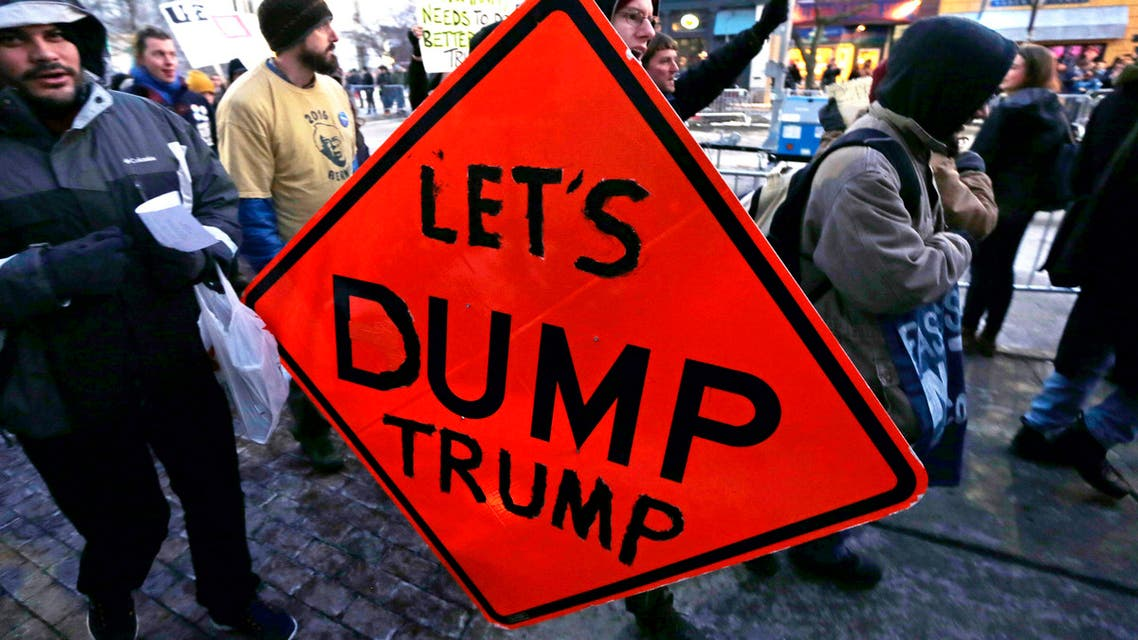 """Johann Kulsic, of Burlington, Vt., carries a """"Let's Dump Trump"""" sign as he marches toward the Flynn Center of the Performing Arts prior to an address by Republican presidential candidate Donald Trump at a campaign stop in Burlington, Thursday, Jan. 7, 2016. (AP)"""