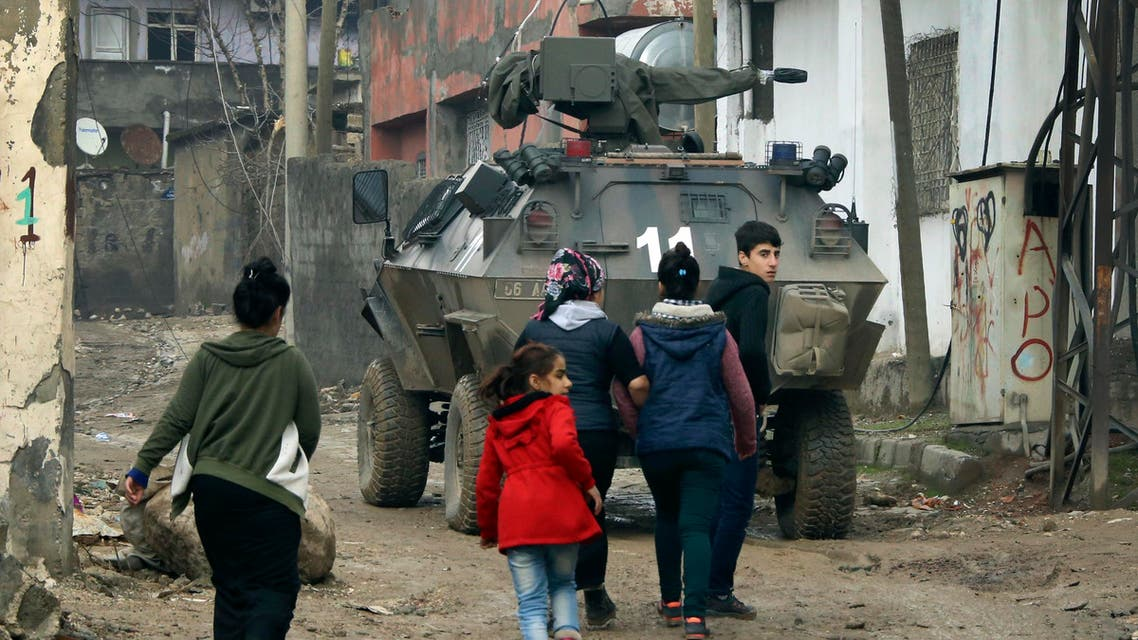 Backdropped by a Turkish forces armoured personnel carrier, residents walk around after the 24-hour curfew was lifted, in the mostly-Kurdish town of Silopi, in southeastern Turkey, near the border with Iraq, Tuesday, Jan. 19, 2016. AP